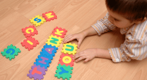 kid on the floor with tile puzzle spelling thank you