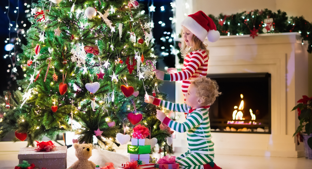 young boy and girl decorating a christmas tree
