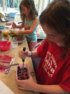 My daughters mash up their cherries and raspberries to create a puree for their popsicles.