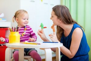 Young mother and her toddler girl playing together with finger toys