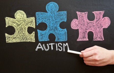 A hand writing the word Autism on a chalkboard under colorful puzzle piece drawings.