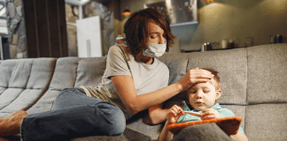 mom with mask on feeling son's forehead
