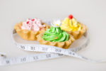 Three colorful green, pink and yellow tart cakes wrapped in measuring tape on white background, unhealthy lifestyle concept, studio