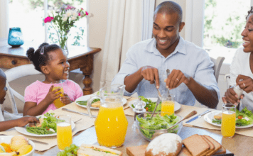 parents with young children eating around a table