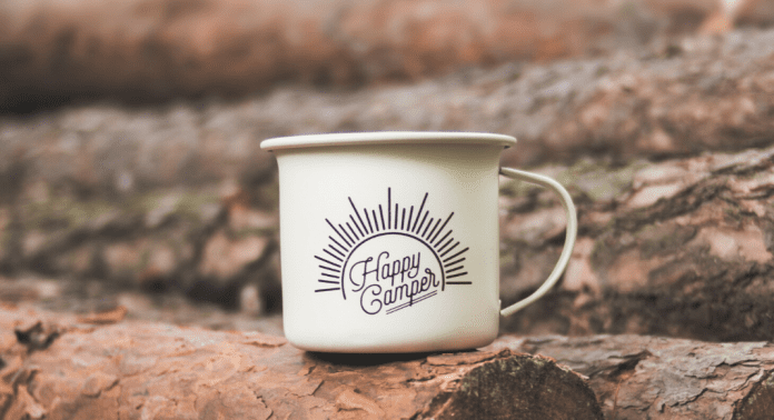 happy camper mug on wood log