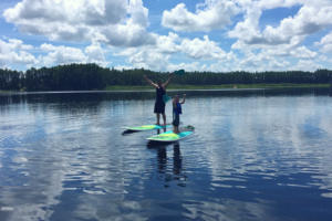 Father son paddleboarding on Florida lake