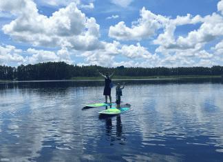 Father son paddleboarding on Florida lake