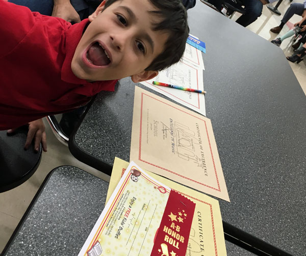 Proud student with his awards certificates