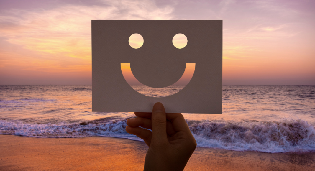 smiling face sign held up for an ocean