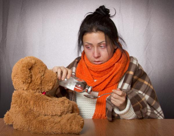women giving medicine to teddy bear