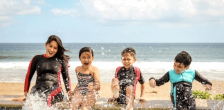 mom and kids splashing in water