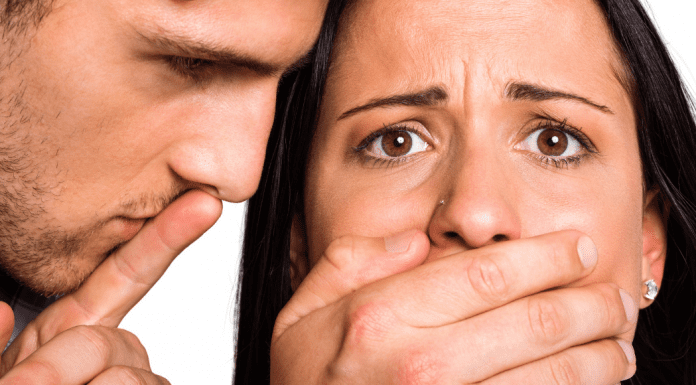 young adult male covering mouth of scared young female