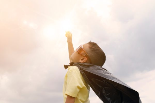 boy raising fist high with a superhero cape