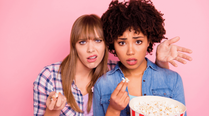 one young white woman , one young black woman eating popcorn and looking surprised shocked