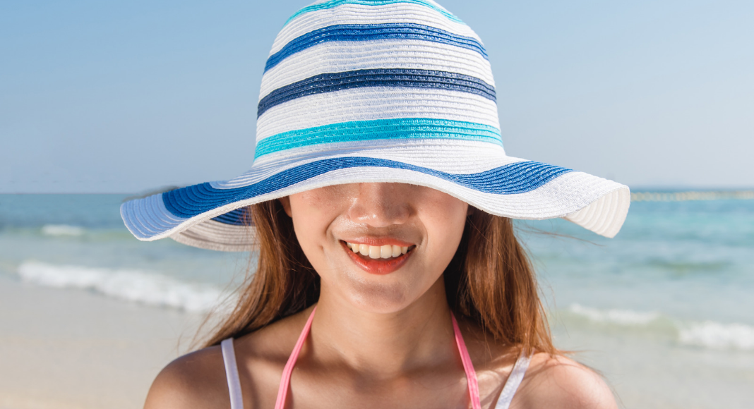 young girl on beach with beach hat over eyes