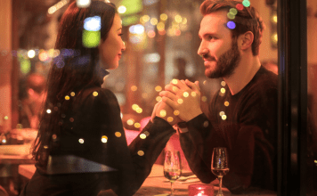 man and woman holding hands at restaurant table