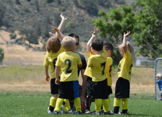 young kids in a soccer huddle with yellow and black soccer uniforms