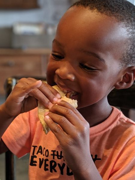 African American young boy eating a taco