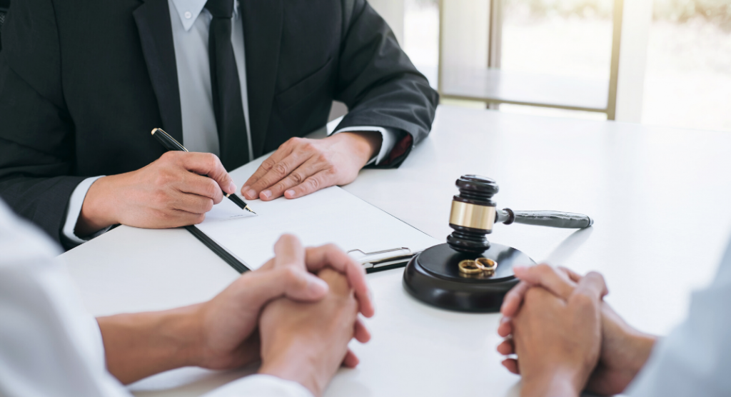table with gavel and wedding rings and attorney with divorce papers