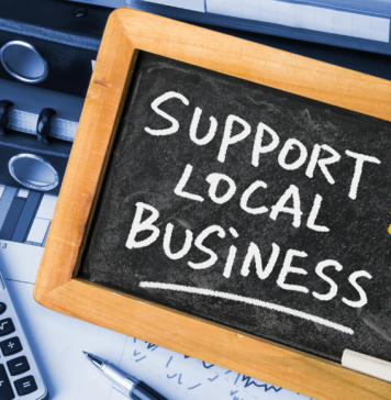 support local business text on blackboard with office accessories behind it