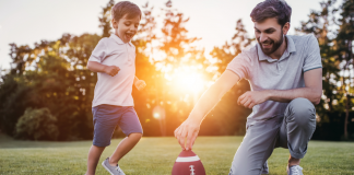 son kicking a football with father