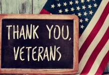 thank you veterans text on chalkboard with american flag behind
