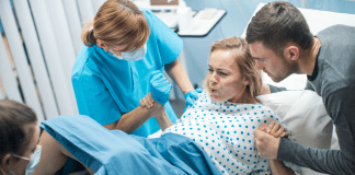 woman in labor with nurse and male partner
