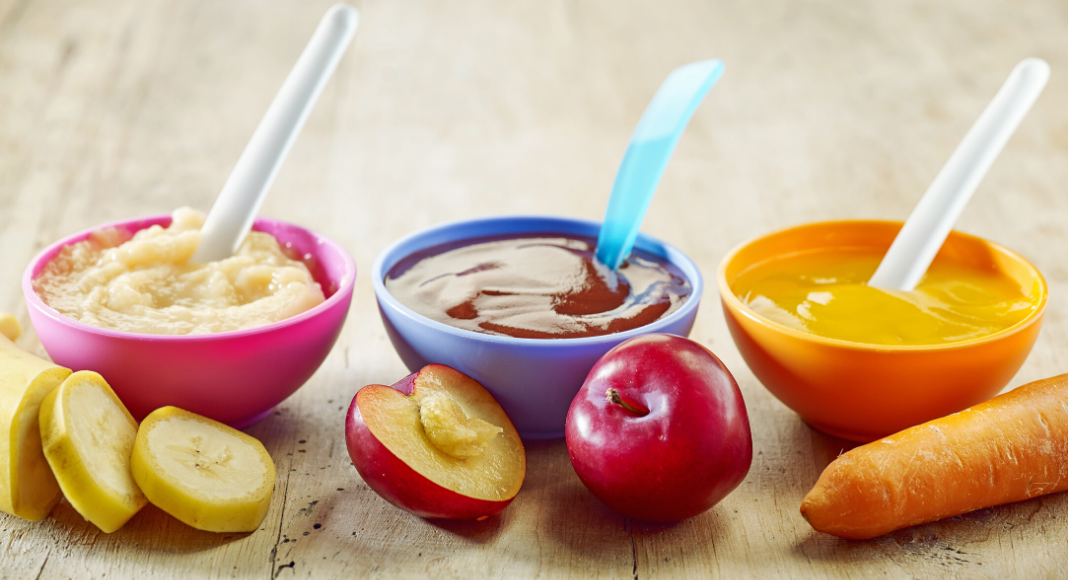 homemade baby food in bowls with spoons