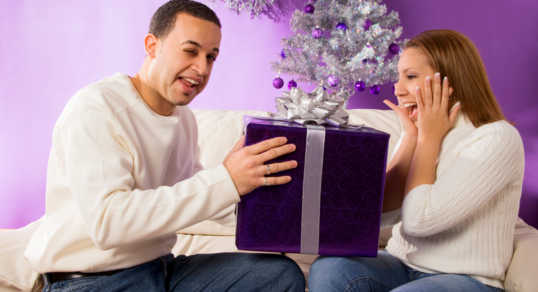 man giving woman gift for christmas