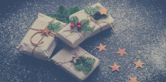 christmas gifts wrapped in brown paper with holly accent and twine