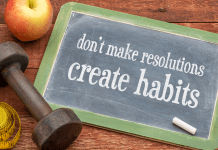 don't make resolutions create habits written on a chalkboard next to an apple, weight and measuring tape