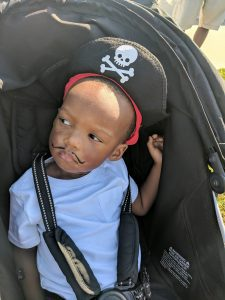 toddler in stroller wearing pirate hat and fake mustache at the Gasparilla parade