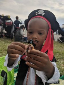 young black boy playing with Lego figurine while dressed as a pirate at the Gasparilla Parade