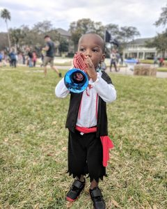 young black boy playing with toy trumpet while dressed as a pirate at the Gasparilla Parade