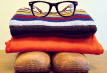 shoes with folded clothes and glasses on top