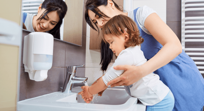 woman and young child hand washing
