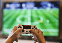 hands on a video game controller in front of a tv