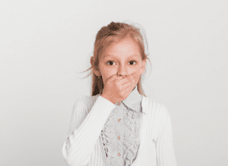 young girl with surprised expression and hand over mouth
