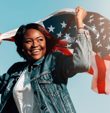 black-smiling-female-raising-hands-with-usa-flag